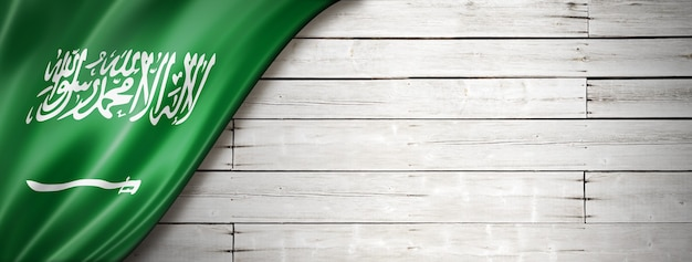 Flaga arabii saudyjskiej na starej białej ścianie. poziomy baner panoramiczny.