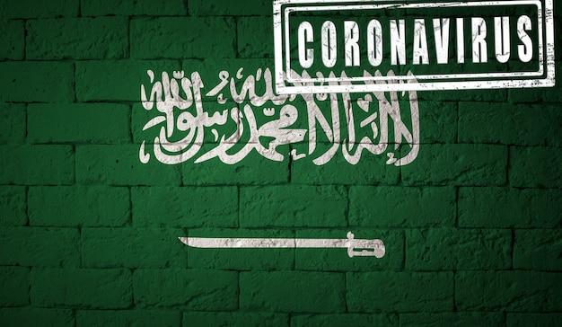 Flaga arabii saudyjskiej o oryginalnych proporcjach. opieczętowane koronawirusem. cegła ściana tekstur. koncepcja wirusa koronowego. na skraju pandemii covid-19 lub 2019-ncov.