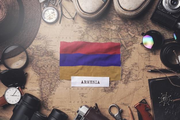 Flaga armenii między akcesoriami podróżnika na starej mapie vintage. strzał z góry
