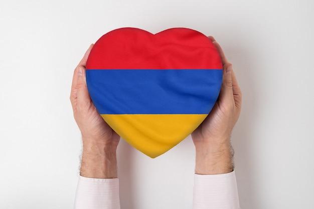 Flaga armenii na pudełku w kształcie serca w męskie dłonie.