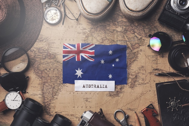 Flaga australii między akcesoriami podróżnika na starej mapie vintage. strzał z góry