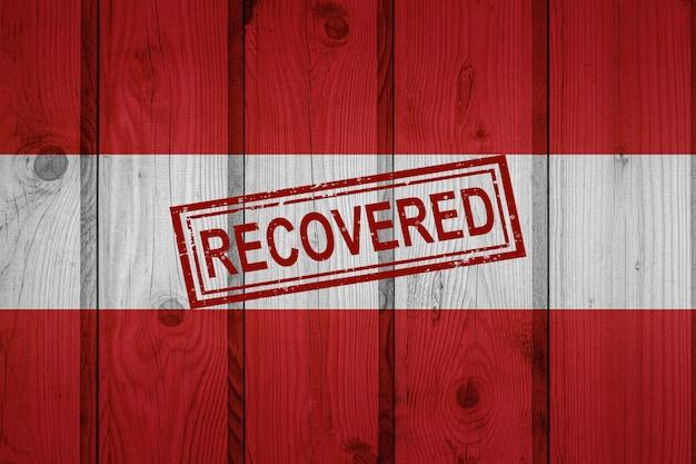 Flaga austrii, która przeżyła lub wyzdrowiała z infekcji epidemii koronawirusa lub koronawirusa. flaga grunge z pieczęcią odzyskane