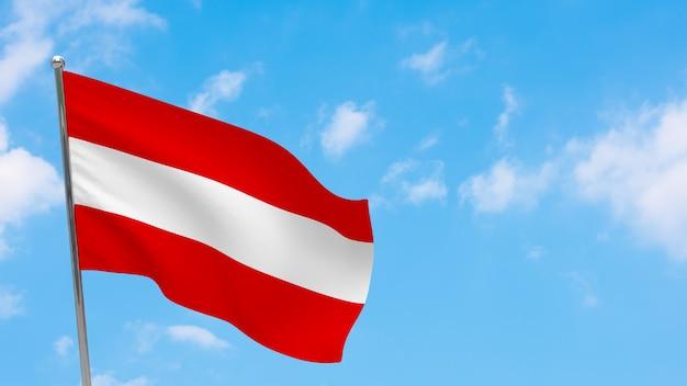 Flaga austrii na słupie. niebieskie niebo. flaga narodowa austrii