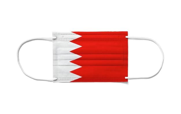 Flaga bahrajnu na jednorazowej masce chirurgicznej. biała powierzchnia na białym tle