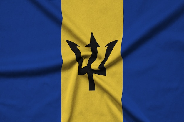 Flaga barbadosu jest przedstawiona na tkaninie z wieloma zakładkami