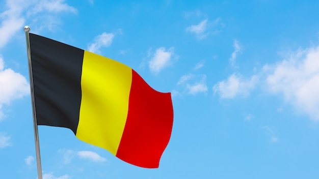 Flaga belgii na słupie. niebieskie niebo. flaga narodowa belgii