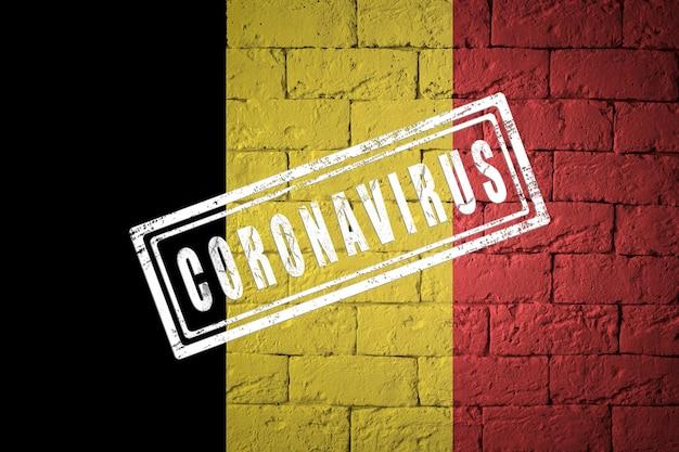 Flaga belgii o oryginalnych proporcjach. opieczętowane koronawirusem. cegła ściana tekstur. koncepcja wirusa koronowego. na skraju pandemii covid-19 lub 2019-ncov.