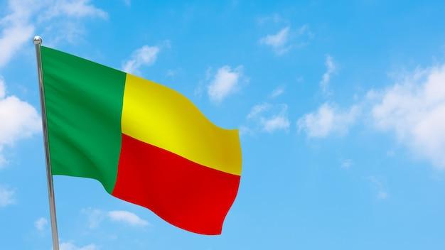 Flaga beninu na słupie. niebieskie niebo. flaga narodowa beninu