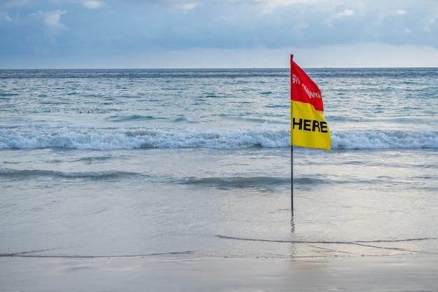 Flaga bezpieczeństwa pływająca tutaj na plaży.