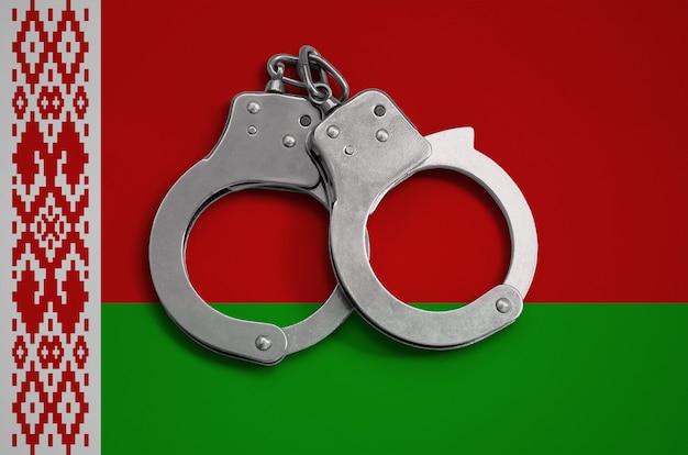 Flaga białorusi i kajdanki policyjne. pojęcie przestrzegania prawa w kraju i ochrona przed przestępczością