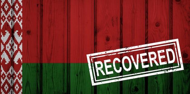 Flaga białorusi, która przeżyła lub wyzdrowiała z zakażenia epidemią koronawirusa lub koronawirusem. flaga grunge z pieczęcią odzyskane