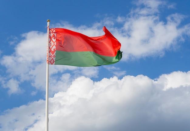 Flaga białorusi na maszcie machającym na tle błękitnego nieba