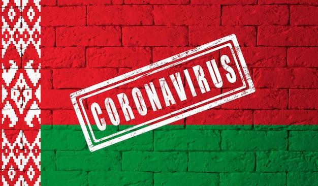 Flaga białorusi o oryginalnych proporcjach. opieczętowane koronawirusem. cegła ściana tekstur. koncepcja wirusa koronowego. na skraju pandemii covid-19 lub 2019-ncov.