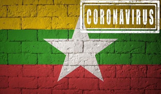 Flaga birmy lub birmy o oryginalnych proporcjach. opieczętowane koronawirusem. cegła ściana tekstur. koncepcja wirusa koronowego. na skraju pandemii covid-19 lub 2019-ncov.