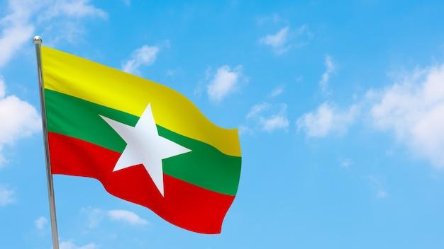 Flaga birmy na słupie. niebieskie niebo. flaga narodowa birmy