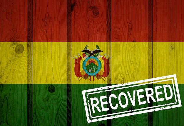 Flaga boliwii, która przeżyła lub wyzdrowiała z infekcji epidemii koronawirusa lub koronawirusa. flaga grunge z pieczęcią odzyskane