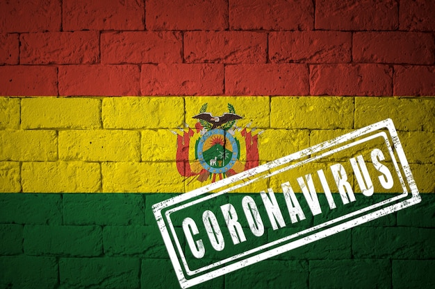 Flaga boliwii o oryginalnych proporcjach. opieczętowane koronawirusem. cegła ściana tekstur. koncepcja wirusa koronowego. na skraju pandemii covid-19 lub 2019-ncov.