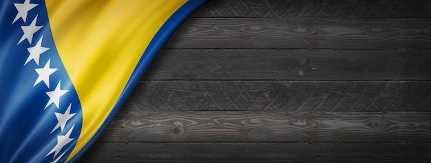 Flaga bośni i hercegowiny na czarnej ścianie z drewna