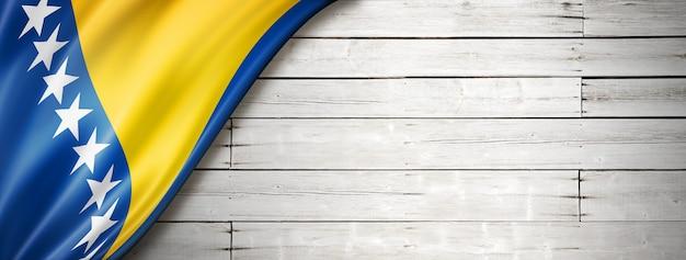 Flaga bośni i hercegowiny na starej białej ścianie. poziomy baner panoramiczny.