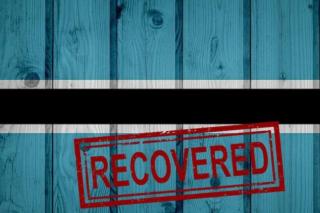 Flaga botswany, która przetrwała lub wyzdrowiała z infekcji epidemii koronawirusa lub koronawirusa. flaga grunge z pieczęcią odzyskane
