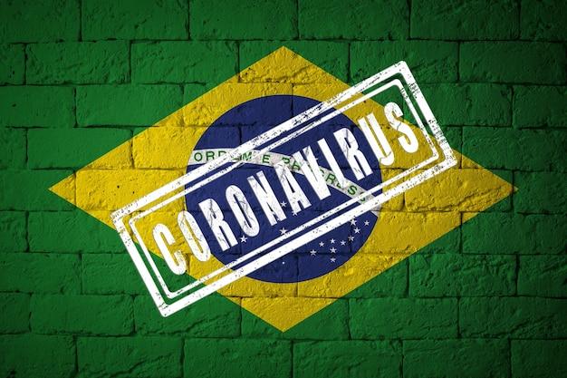 Flaga brazylii o oryginalnych proporcjach. opieczętowane koronawirusem. cegła ściana tekstur. koncepcja wirusa koronowego. na skraju pandemii covid-19 lub 2019-ncov.
