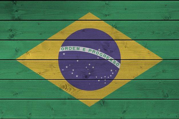 Flaga brazylii przedstawiona w jasnych kolorach farby na starej drewnianej ścianie. baner z teksturą