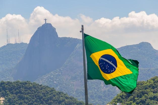 Flaga brazylii z wizerunkiem chrystusa odkupiciela w tle w rio de janeiro, brazylia