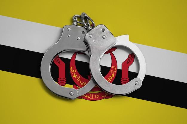 Flaga brunei darussalam i kajdanki policyjne. pojęcie przestrzegania prawa w kraju i ochrona przed przestępczością
