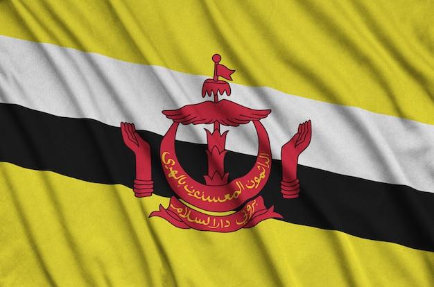 Flaga brunei darussalam jest przedstawiona na sportowej tkaninie z wieloma zakładkami.