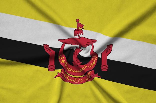 Flaga brunei darussalam jest przedstawiona na tkaninie sportowej z wieloma zakładkami.