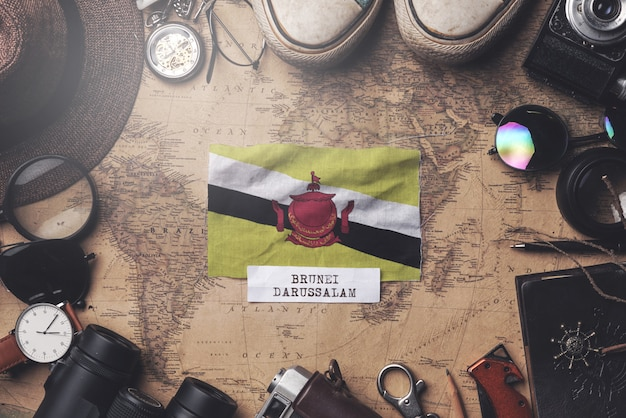 Flaga brunei między akcesoriami podróżnika na starej mapie vintage. strzał z góry