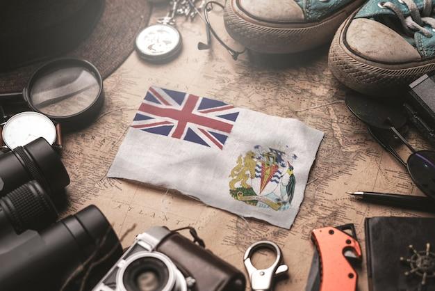 Flaga brytyjskiego terytorium antarktycznego między akcesoriami podróżnika na starej mapie vintage. koncepcja miejsca turystycznego.
