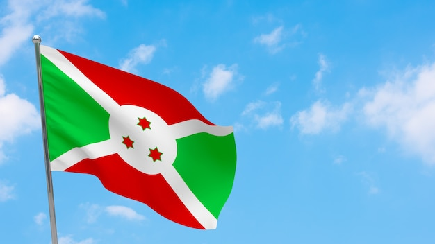 Flaga burundi na słupie. niebieskie niebo. flaga narodowa burundi