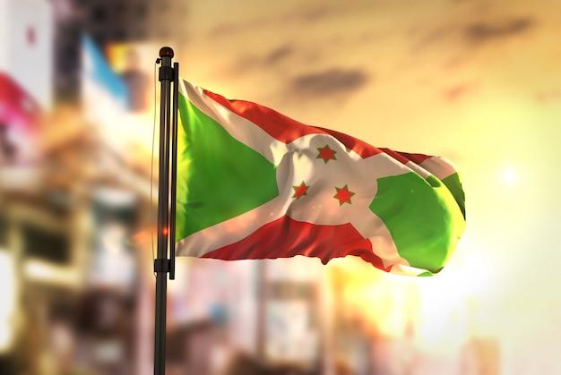 Flaga burundi przeciw miastu rozmyte tło w sunrise backlight