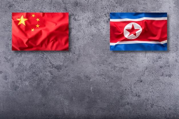 Flaga chin i korei północnej na tle konkretnych.