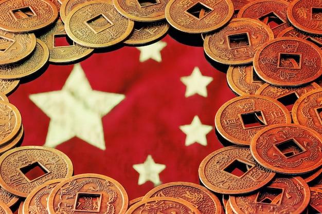 Flaga chin otoczona szczęśliwymi monetami feng shui. pojęcie gospodarki chińskiej.