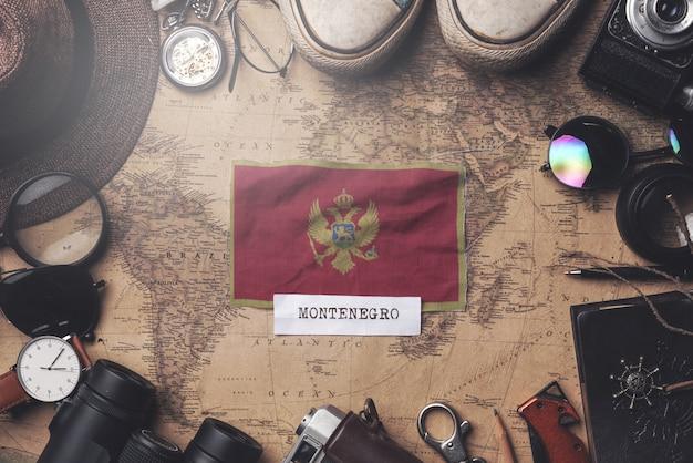 Flaga czarnogóry między akcesoriami podróżnika na starej mapie vintage. strzał z góry