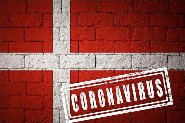 Flaga danii o oryginalnych proporcjach. opieczętowane koronawirusem. cegła ściana tekstur. koncepcja wirusa koronowego. na skraju pandemii covid-19 lub 2019-ncov.
