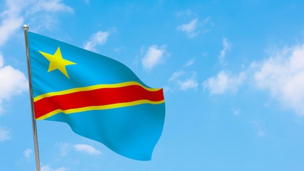 Flaga demokratycznej republiki konga na słupie. niebieskie niebo. flaga narodowa demokratycznej republiki konga