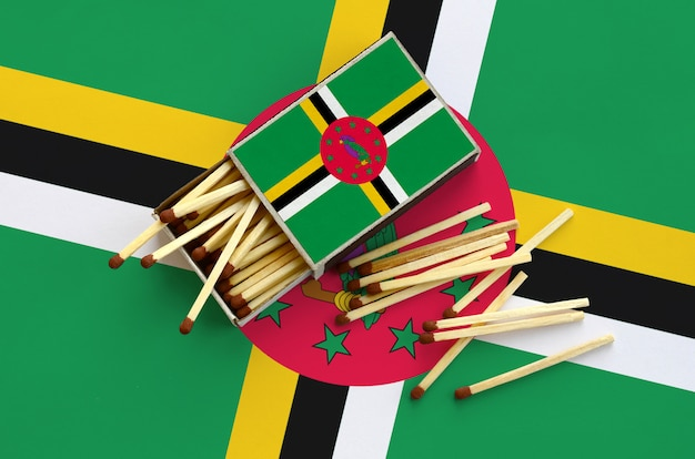 Flaga dominiki jest pokazana na otwartym pudełku zapałek, z którego wypada kilka zapałek i leży na dużej flagi