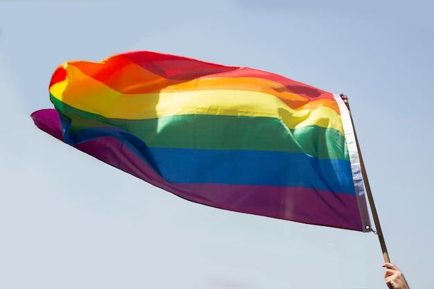 Flaga dumy gejowskiej na tle niebieskiego nieba
