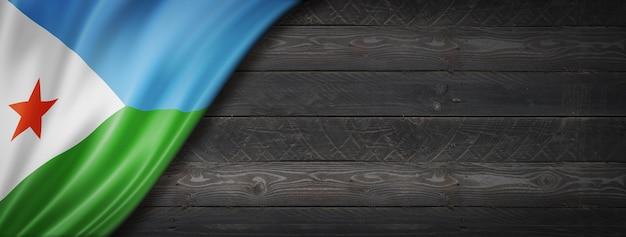 Flaga dżibuti na czarnej ścianie z drewna
