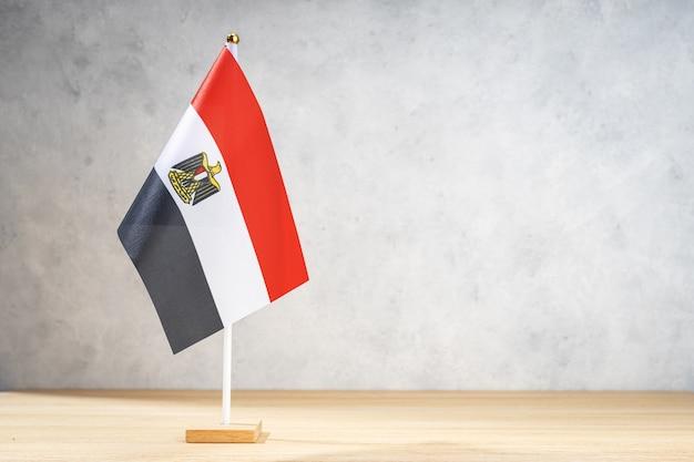 Flaga egiptu stół na białej ścianie z teksturą. skopiuj miejsce na tekst, projekty lub rysunki