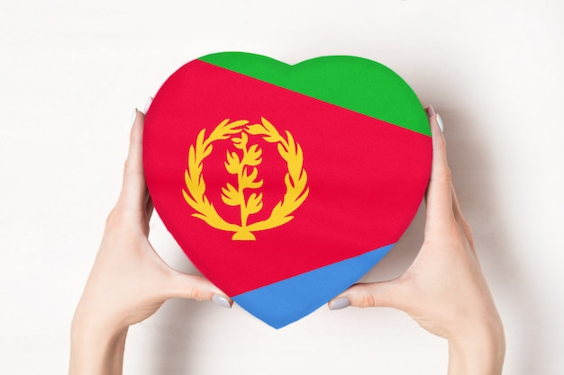 Flaga erytrei na pudełku w kształcie serca w rękach kobiet.