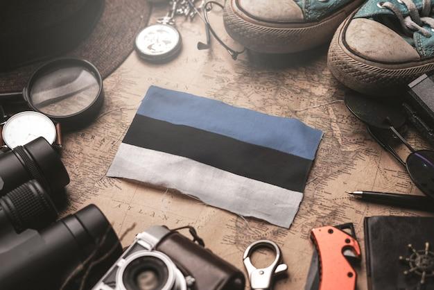 Flaga estonii między akcesoriami podróżnika na starej mapie vintage. koncepcja miejsca turystycznego.