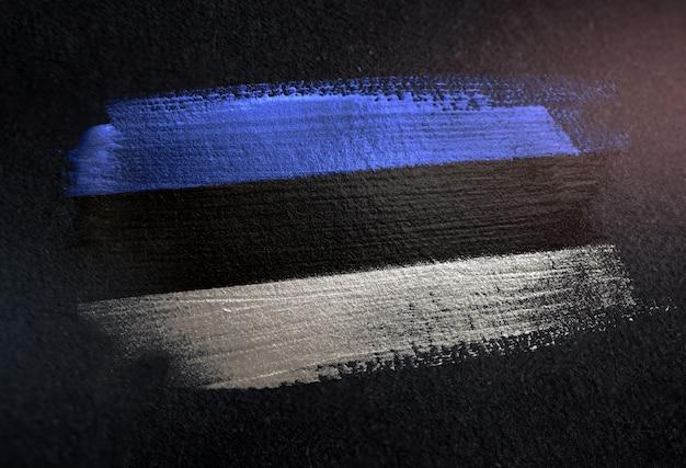 Flaga estonii z pędzlem metalicznej farby na ciemnej ścianie grunge