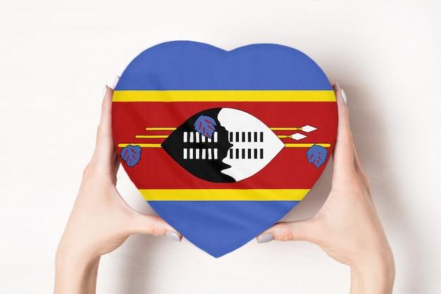 Flaga eswatini na pudełku w kształcie serca w rękach kobiet