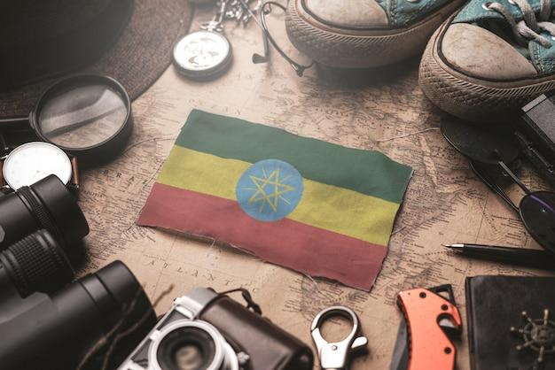 Flaga etiopii między akcesoriami podróżnika na starej mapie vintage. koncepcja miejsca turystycznego.