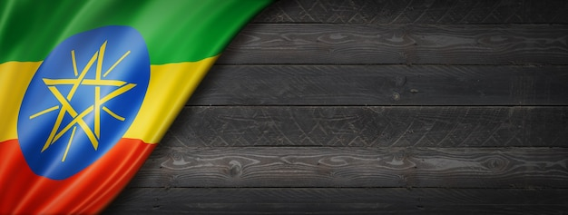 Flaga etiopii na czarnej ścianie z drewna. poziomy baner panoramiczny.
