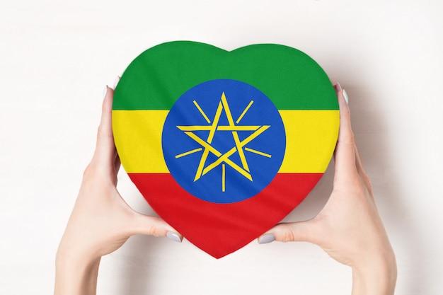Flaga etiopii na pudełku w kształcie serca w rękach kobiet.